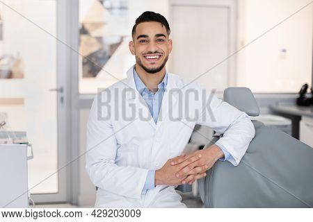 Portrait Of Handsome Arab Stomatologist Doctor Posing In Dental Clinic Interior