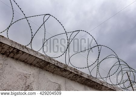 Barbed Wire On A Concrete Fence With A Gray Sky. Democracy Dictatorship And Persecution Concept
