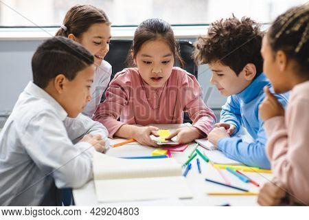 Diverse Small Schoolchildren Using Mobile Phone At Classroom