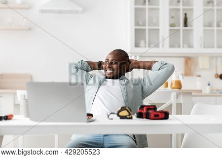 Handyman Blogger. Excited African American Man Resting With Hands Behind Head After Working On Lapto