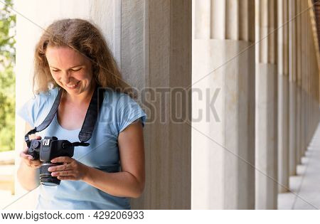 Tourist In Stoa Of Attalos, Athens, Greece, Europe. Happy Young Woman Plays Images In Camera At Anci