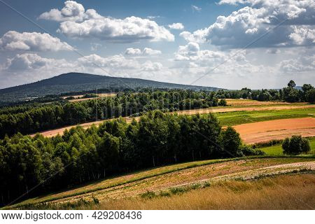 A Picturesque Countryside Panorama. Hilly, Golden Fields, Green Forest, Cloudy Sky. Swietokrzyskie M