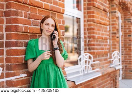 Medium Shot Portrait Of Attractive Young Woman Talking On Mobile Phone Standing Leaning On Old Red S