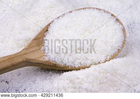Salt In Wooden Spoon. Salt Background Scattered White Salt Spices.