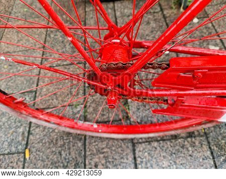 Selective Focus Close Up View At A Red Bicycle Wheel With Metal Spokes.