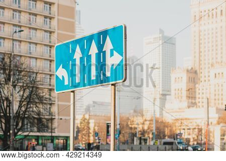 Blue Traffic Sign Indicating Rules Of Turn On The Traffic Lanes And City On The Background. Highway.