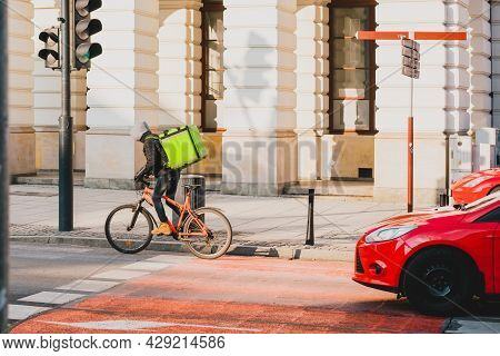 Food Delivery Bicycle Driver With Green Backpack Moves Forward On The Green Traffic  Light Signal. R