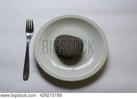 White Plate With A Gray Stone And Fork On White Background. Heavy Food Concept. Bad Nutrition.