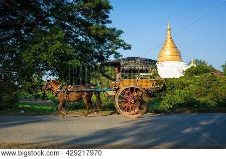 Inwa (Ava), Myanmar - January 10, 2019: Burmese man riding horse cart with big wooden wheels on road with view of Shwezigon Pagoda