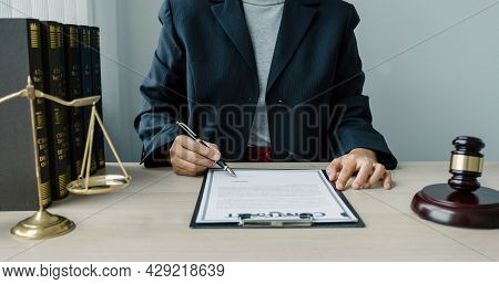 The Woman Lawyer Is Sitting At The Desk In The Office With A Justice Scale And Gavel Hammer. Study T