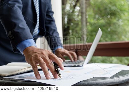 Businessman Hand Holding Pen, Analysis The Graph With Laptop At The Home Office For Setting Challeng