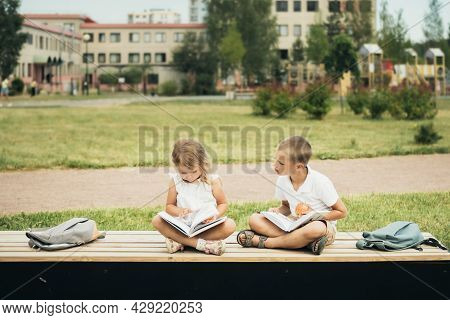 Two Caucasian Little Students, Boy And Girl, Eating Apples During School Break And Reading Books.  S
