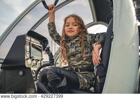 Smiling Tween Girl In Camouflage Dress Sitting In Helicopter Cockpit