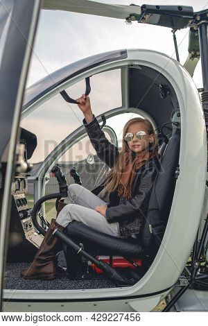 Confident Tween Girl In Mirrored Sunglasses Sitting In Open Helicopter