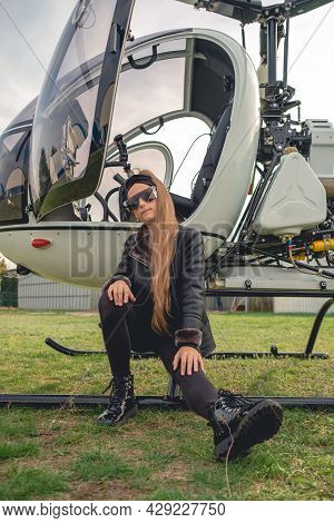 Tween Girl Sitting On Footboard Of Open Helicopter