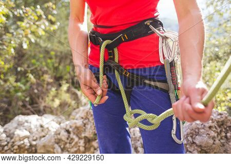 A Girl Rock Climber Ties Herself With A Rope To The Harness For Safe Climbing In The Mountains. Safe