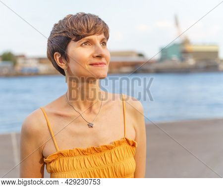 Portrait Of Beautiful Mature Woman In Open Dress With Short Hair Standing On River Embankment In Cit
