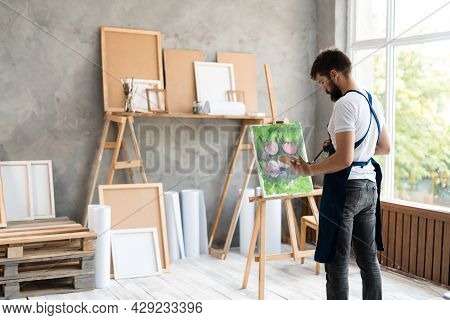 In A Creative Art Studio, A Bearded Man Artist Stands Holding A Brush And A Palette With Paints, Pai