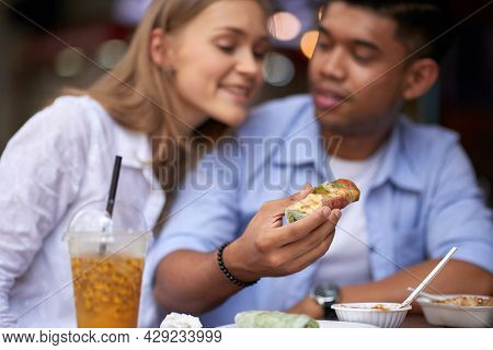 Multi-ethnic Young Couple Enjoying Delicious Spring Rolls With Sauces In Outdoor Cafe