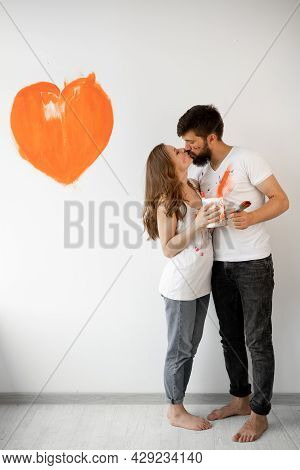 Happy Married Couple In Love In White T-shirts Makes Repairs, Renewing The Painting Of The Walls, Mo