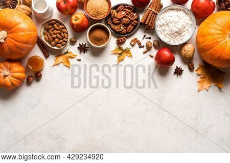 Autumn Fall Baking Background With Pumpkins, Apples, Nuts, Food Ingredients And Seasonal Spices. Coo
