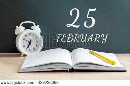 February 25. 25-th Day Of The Month, Calendar Date.a White Alarm Clock, An Open Notebook With Blank