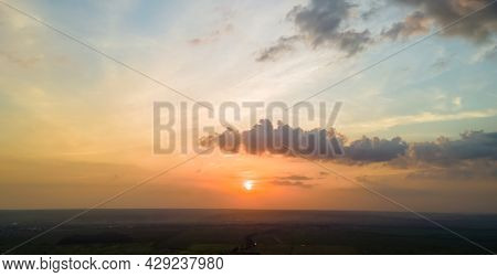 Bright Colorful Sunset Sky With Setting Sun And Vibrant Clouds Over Dark Landscape.