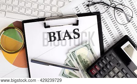 Text Bias On Office Desk Table With Keyboard, Dollars,calculator ,supplies,analysis Chart On White B