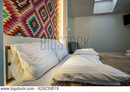Interior Of A Spacious Hotel Bedroom On Attic Floor With Fresh Linen On A Big Double Bed. Cozy Conte