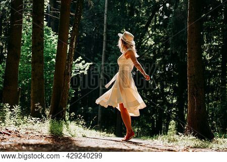 A Young Woman In A White Dress And A Straw Hat Walks Through The Woods. Fairy Forest. Side View