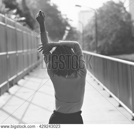 Rear view of skinny girl stretching on the street