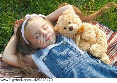 Pretty Little Child Girl With Closed Eyes Laying Down With Her Teddy Bear Toy On Blanket On Green Gr