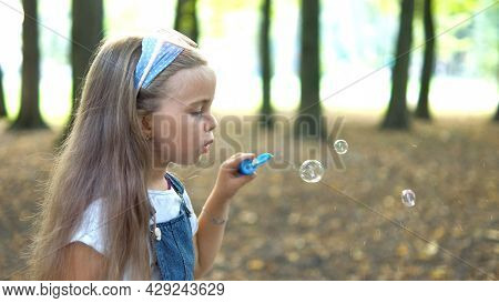 Happy Little Child Girl Blowing Soap Bubbles Outside In Green Park. Outdoor Summer Activities For Ch