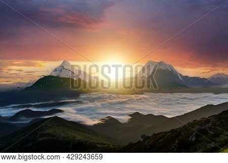 Sunset Landscape With High Peaks And Foggy Valley With Thick White Clouds Under Vibrant Colorful Eve