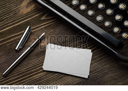 Stack Of Blank White Business Cards With Typewriter And Fountain Pen On Wooden Table. Mock-up Templa