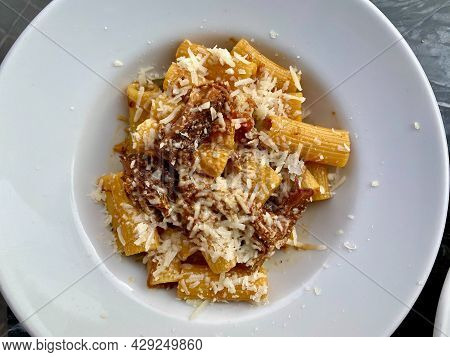 Rigatoni Pasta Alla Genovese, A Typical Neapolitan Recipe With Parmesan Cheese, Onions And Meat In A