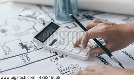 Male engineer or architect is pressing a calculator to calculate the building's structure and balanc