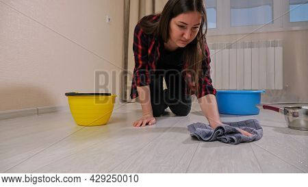 Upset Lady In Shirt Wipes Water Flowing From Ceiling After Rain With Rug Near Containers On Floor In
