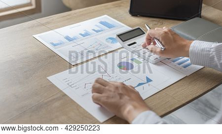Young Asian businessman presses a calculator to calculate income tax and corporate income in a priva