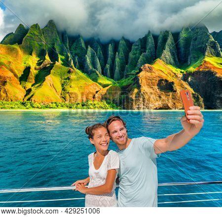 Hawaii cruise ship couple tourists taking selfie photo with phone at Na Pali Coast, Kauai island, USA summer vacation travel. Happy Asian woman, Caucasian man, interracial friends group of people.