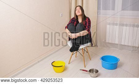 Water Damage. Upset Woman Sits On Chair Near Containers In Light Living Room. Water Drips From The C
