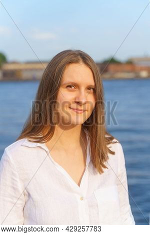 Portrait Of Beautiful Young Woman With Long Blonde Hair Standing On River Embankment In City Of St.