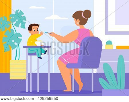 Baby Feeding Room. Mom Gives Food Toddler With Spoon At Home, Little Kid Sitting On High Chair, Harm