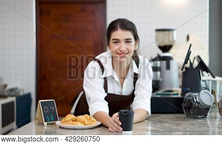 Young Caucasian Coffee Shop Staff Dressed In Brown Apron Handed A Cup Of Coffee And Croissant Plate