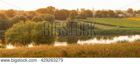 Autumn Rural Landscape - Small Country Lake With A Meadow At Sunset. Houses In Village And Agricultu
