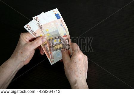 Euro Notes In Wrinkled Hands Of Elderly Woman. Concept Of Pension Payments, Savings At Retirement, A