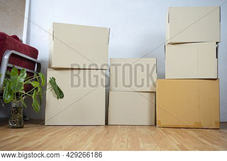 Cardboard Boxes - Moving To A New House. Moving Boxes With Belongings In Empty Room