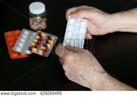 Wrinkled Hands Of Elderly Woman With Pills On Dark Wooden Table. Different Medication In Tablets And