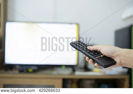 The Women With The Remote Control In Hand Watching The Channel And Presses The Button On The Remote