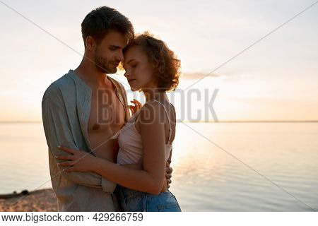 Sensual Young Caucasian Couple Hugging Each Other During Date On Beach At Sunset. Romantic Date Conc
